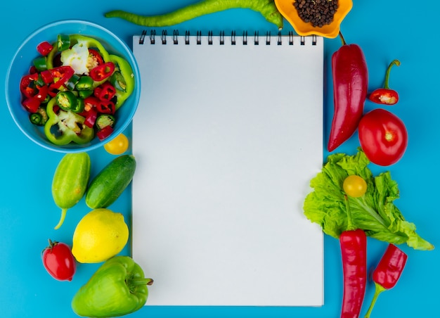 Top view of vegetables as cucumber pepper tomato lettuce with black pepper seeds and sliced peppers with note pad on blue surface with copy space