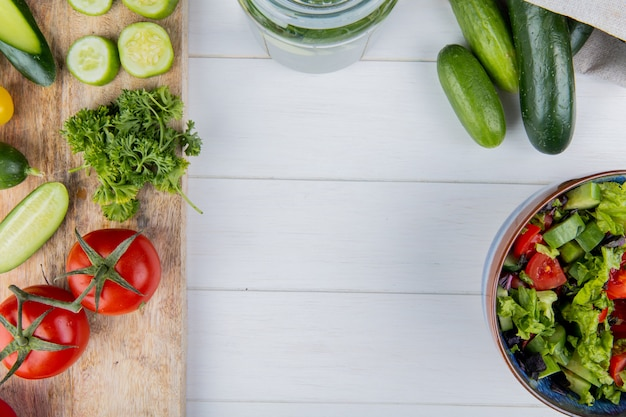 Top view of vegetables as cucumber tomato coriander on cutting board and cucumbers in sack with vegetable salad on wooden surface with copy space