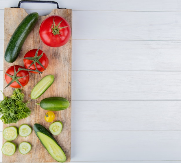 Top view of vegetables as cucumber tomato coriander on cutting board on left side and wooden surface with copy space