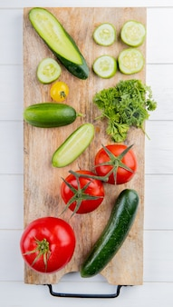 Top view of vegetables as cucumber tomato coriander on cutting board on wood
