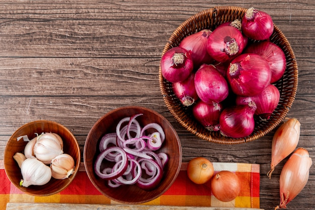 Top view of vegetables as different types of onion and garlic on wooden background with copy space