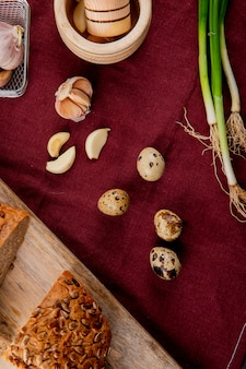 Top view of vegetables as egg garlic scallion with black bread on burgundy background