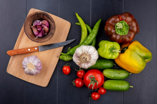 Top view of vegetables as garlic bulb and cloves with knife on cutting board and tomato pepper cucumber on black surface