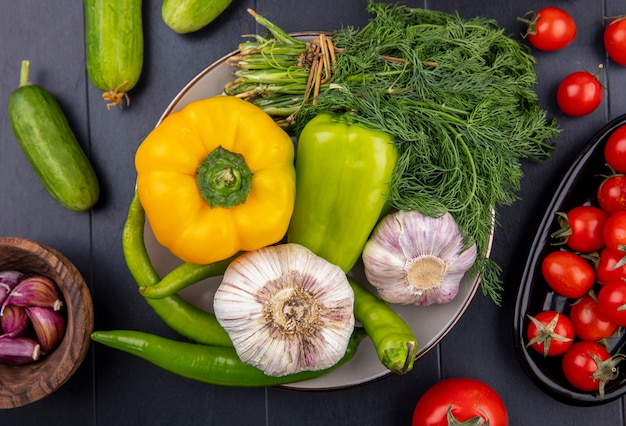 Top view of vegetables as garlic pepper dill in plate with garlic cloves cucumbers and tomatoes on black surface