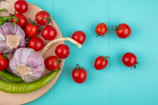 Top view of vegetables as garlic pepper tomato on cutting board on blue surface