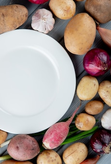 Top view of vegetables as garlic potato onion radish with empty plate on wooden background