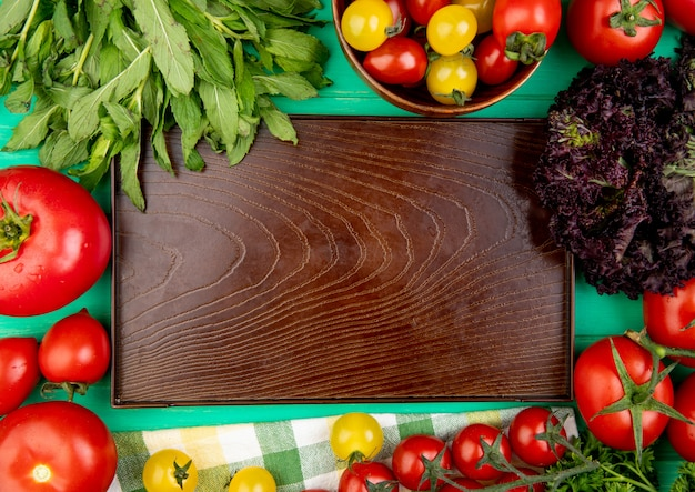 Top view of vegetables as green mint leaves basil tomato around empty tray on green surface