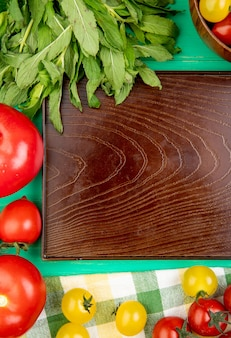 Top view of vegetables as green mint leaves tomatoes around empty tray on green