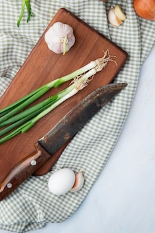 Top view of vegetables as green onion garlic egg with knife on cloth on white background with copy space