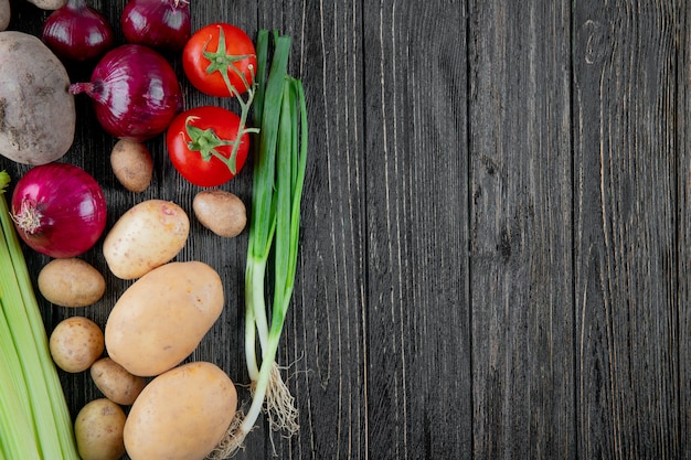 Top view of vegetables as onion potato celery tomato and scallion on left side and wooden background with copy space