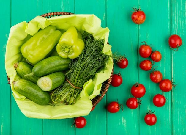 Vista superiore delle verdure come merce nel carrello dell'aneto del cetriolo del pepe con i pomodori su superficie verde