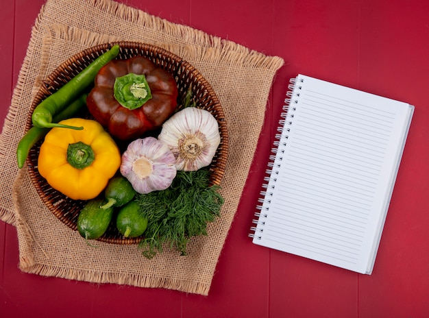 Top view of vegetables as pepper cucumber garlic dill in basket on sackcloth and note pad on red surface