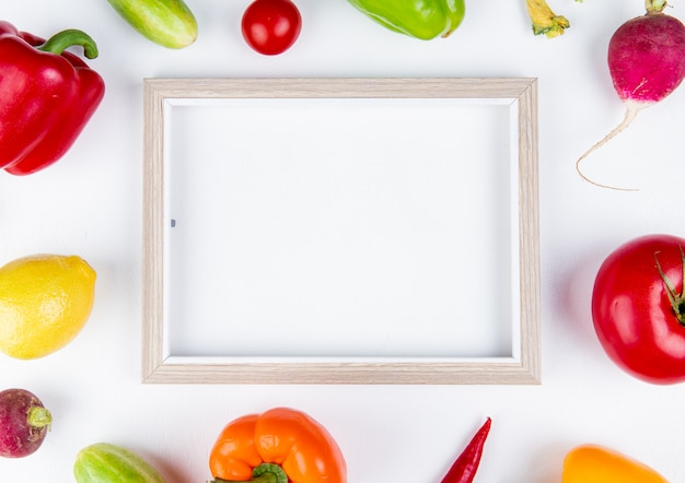 Top view of vegetables as pepper cucumber radish tomato with frame on white surface with copy space