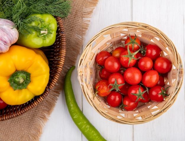 Vista superiore delle verdure come merce nel carrello dell'aneto dell'aglio del pepe su tela di sacco con il canestro dei pomodori su superficie di legno