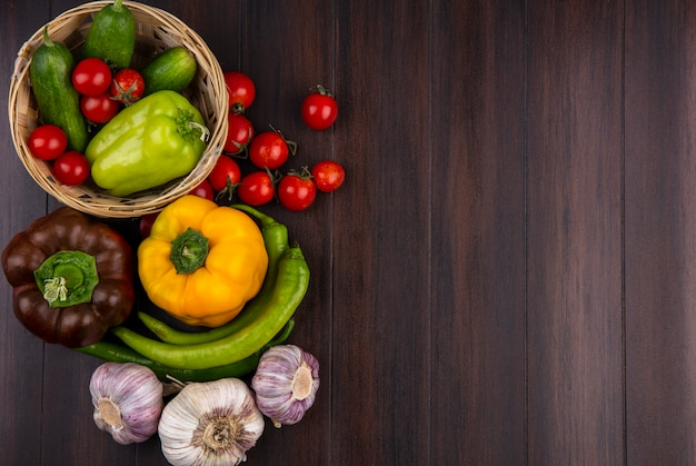 Top view of vegetables as pepper tomato cucumber garlic in basket and on wooden surface