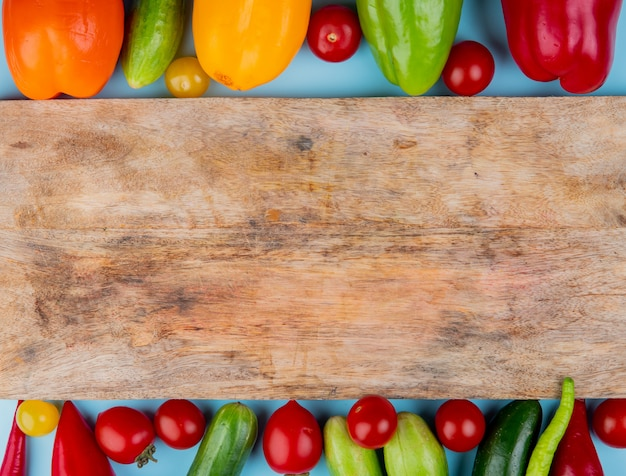 Top view of vegetables as pepper tomato cucumber with cutting board on blue surface