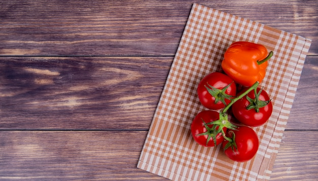 Top view of vegetables as pepper and tomatoes on plaid cloth on right side and wooden surface with copy space