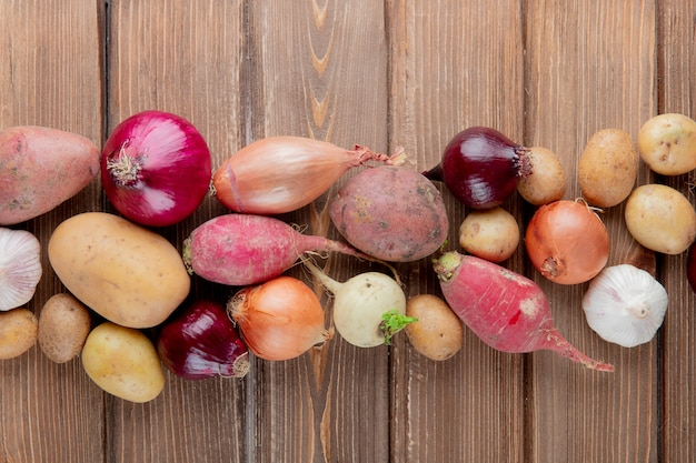 Top view of vegetables as potato radish onion garlic on wooden background