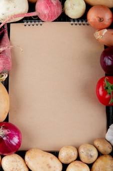 Top view of vegetables as radish onion tomato potato with note pad on center with copy space