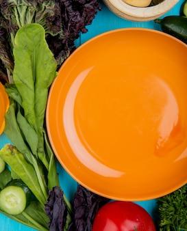 Vista superiore delle verdure come pomodoro del cetriolo del basilico degli spinaci con il piatto sul blu