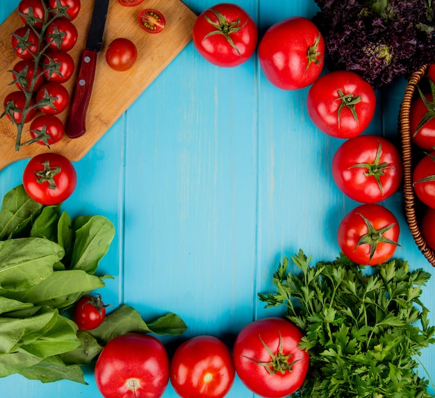 Top view of vegetables as spinach basil tomato coriander with knife on cutting board on blue with copy space