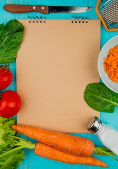 Top view of vegetables as spinach tomato carrot lettuce with salt knife metal grater with note pad on blue background with copy space