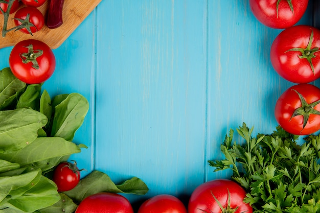 Top view of vegetables as spinach tomato coriander with knife on cutting board on blue surface with copy space