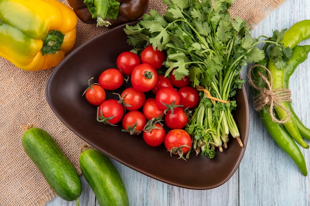 Top view of vegetables as tomato bunch of coriander in bowl with peppers on sackcloth and on wooden surface