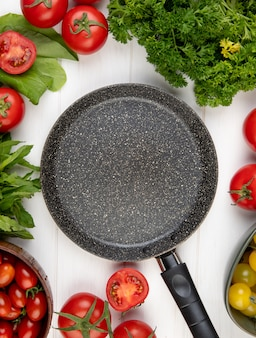 Top view of vegetables as tomato coriander spinach green mint leaves with frying pan on center on wooden surface