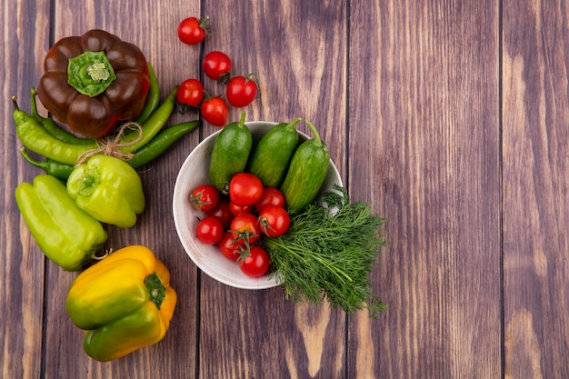 Top view of vegetables as tomato cucumber dill in bowl with peppers on wooden surface