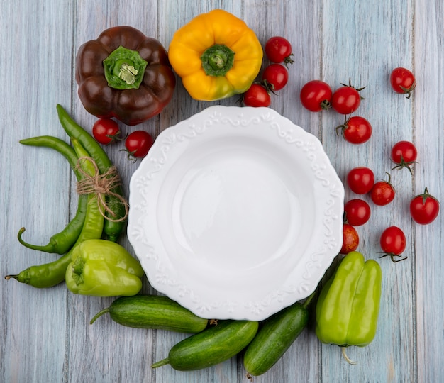 Top view of vegetables as tomato cucumber pepper around empty plate on wooden surface