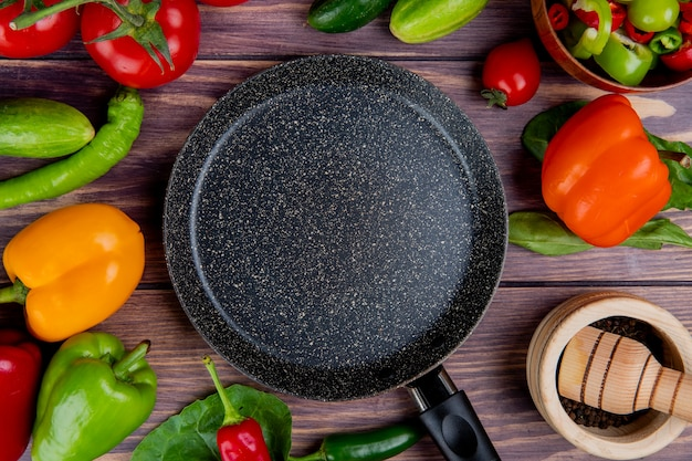 Top view of vegetables as tomato cucumber pepper with leaves and black pepper in garlic crusher and frying pan on wood