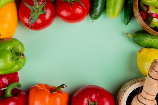 Vista superiore delle verdure come pepe del cetriolo del pomodoro con il limone e il pepe nero in frantoio dell'aglio su superficie verde con lo spazio della copia