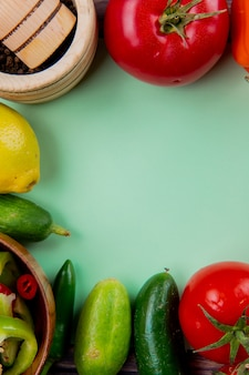 Top view of vegetables as tomato cucumber pepper with lemon and black pepper in garlic crusher on green surface with copy space