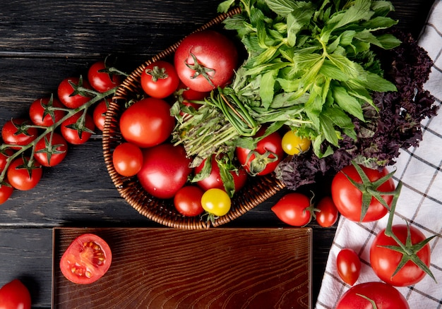Top view of vegetables as tomato green mint leaves basil in basket and cut tomato in tray on wooden surface