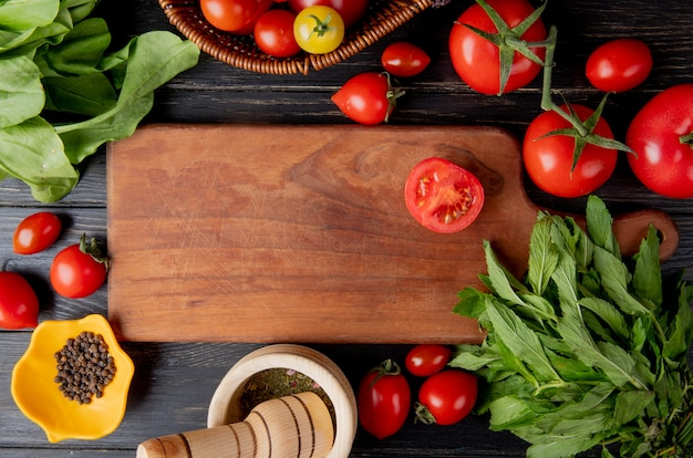 Top view of vegetables as tomato and green mint leaves with black pepper seeds and garlic crusher and cut tomato on cutting board on wooden surface