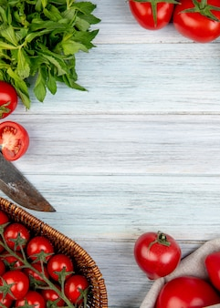 Top view of vegetables as tomato green mint leaves with knife on wooden surface with copy space