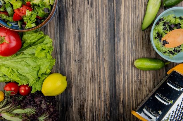 Vista superiore delle verdure come basilico della lattuga al pomodoro con le insalate e la grattugia di verdure del limone su superficie di legno con lo spazio della copia