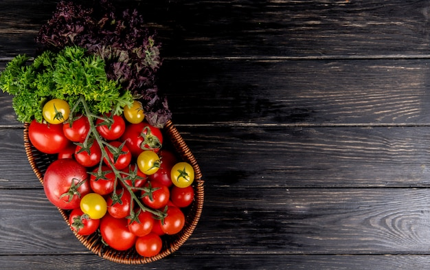 Top view of vegetables as tomatoes coriander basil in basket on wooden surface with copy space