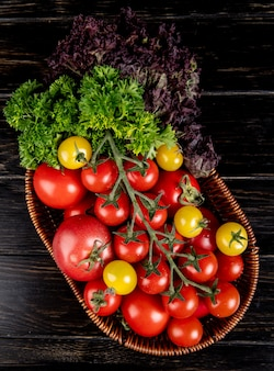 Top view of vegetables as tomatoes coriander basil in basket on wooden surface