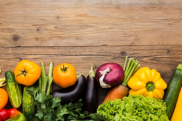 Top view vegetables assortment on wooden background