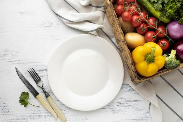 Корзина с овощами и тарелка, вид сверху