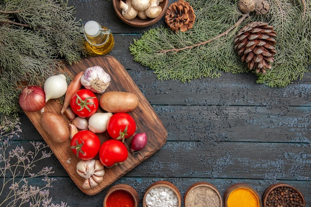 Top view vegetables and branches cutting board and vegetables on it between colorful spices and oil bowl of white mushrooms and spruce branches