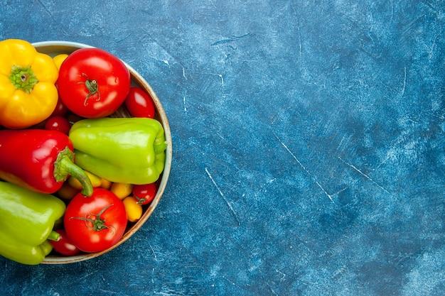 Vista superiore verdure pomodorini cumcuat diversi colori peperoni pomodori sul piatto di legno sul tavolo blu con spazio libero