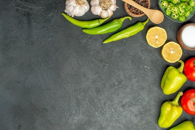 暗い背景にトップビュー野菜組成トマトピーマンとニンニク