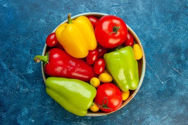 Vista dall'alto verdure diversi colori peperoni pomodori pomodorini in una ciotola sul tavolo blu con copia spazio