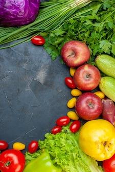 Vista dall'alto frutta e verdura pomodorini cumcuat mele cavolo rosso cipolla verde lattuga prezzemolo con spazio libero