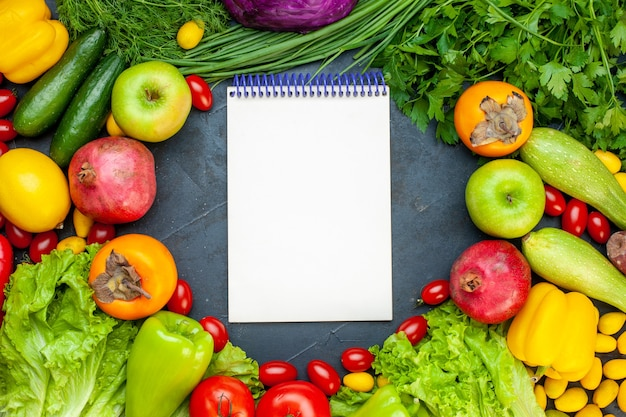 Top view vegetables and fruits lettuce tomatoes cucumber dill cherry tomatoes zucchini pomegranate persimmon apple notebook on center
