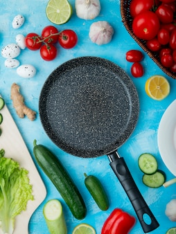 Top view of vegetables and frying pan on blue surface