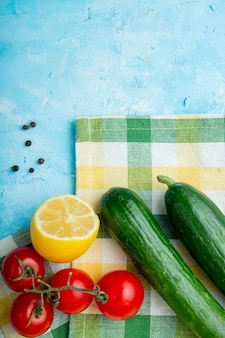 Top view of vegetables, lemon and pepper spice on cloth on blue surface